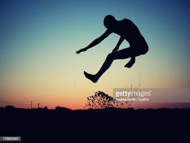 Full Length Of Silhouette Man Jumping Against Sky During Sunset