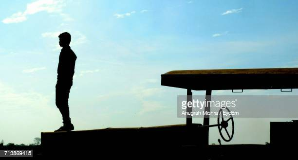 Full Length Of Silhouette Man Standing On Tractor Against Sky