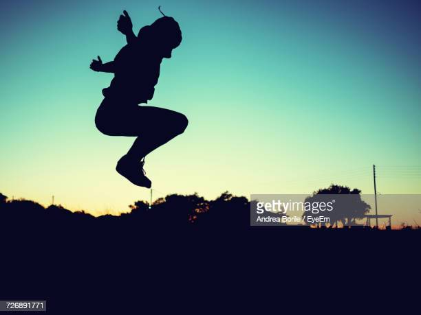Full Length Of Silhouette Person Jumping Against Sky During Sunset
