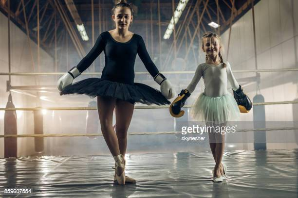 Full length of smiling ballet dancers in a boxing ring.