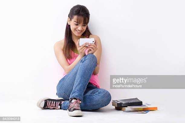 Full length of smiling female college student reading text message