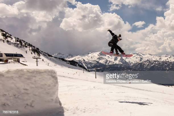 Full Length Of Snowboarder Jumping Against Cloudy Sky At Snowcapped Mountain