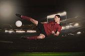 Full length of soccer player kicking ball during match