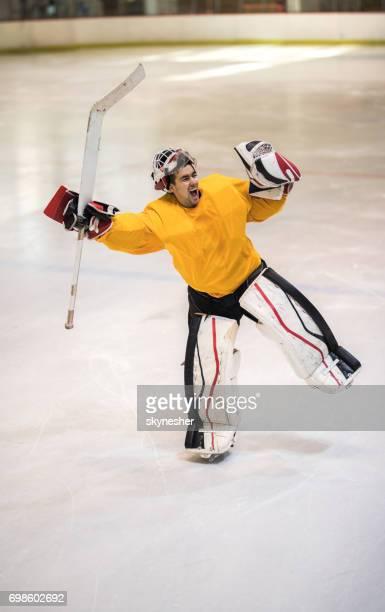 Full length of successful ice hockey goalie screaming of joy in a rink.