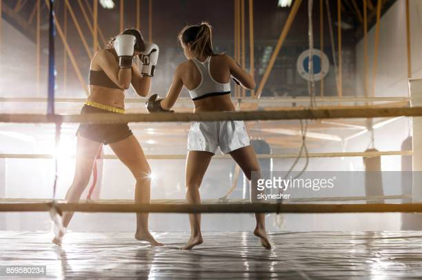 Full length of two women dueling on a boxing match in health club.