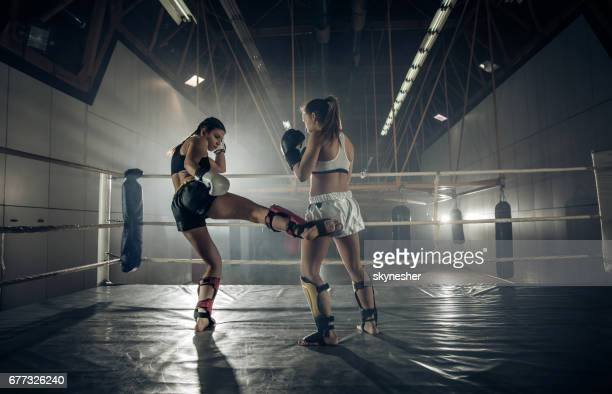 Full length of two women fighting on a boxing match in a gym.