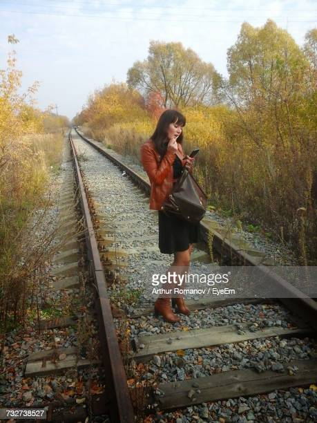 Full Length Of Woman Applying Lipstick While Standing On Railroad Track