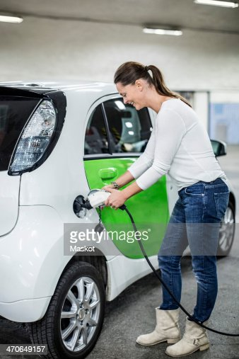 Full length of woman charging electric car at gas station