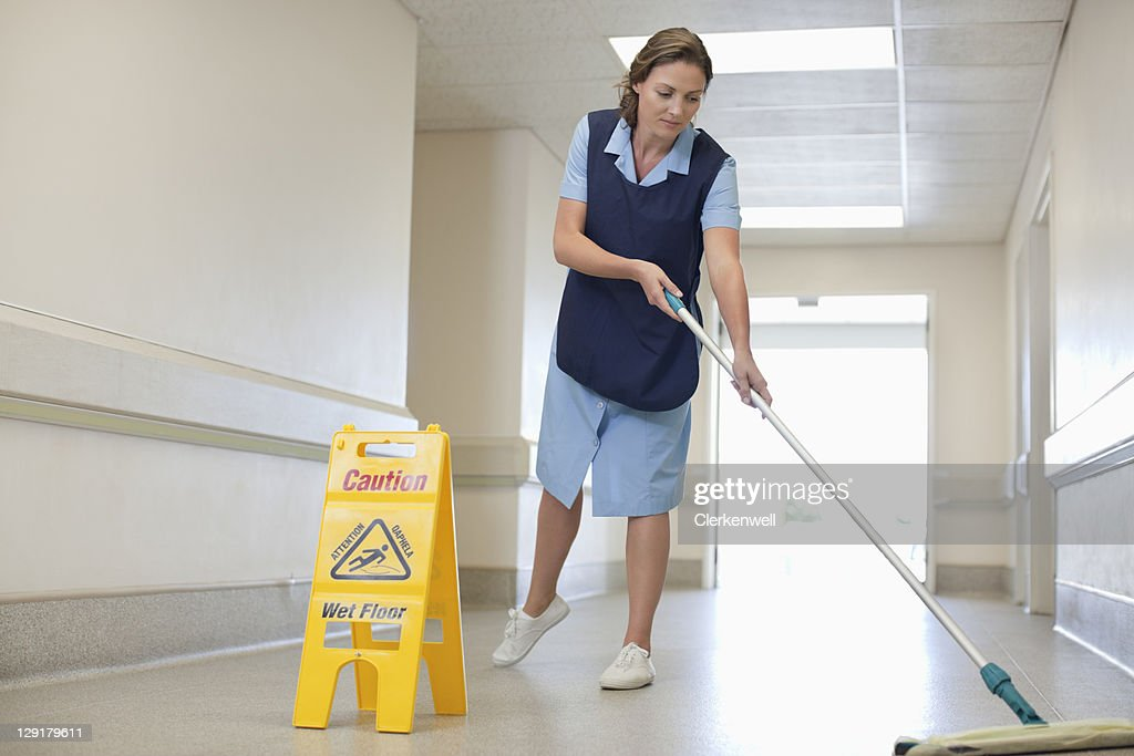 Full length of woman cleaning hospital floor : Stock Photo