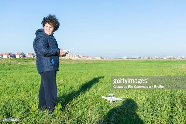 Full Length Of Woman Controlling Quadcopter While Standing On Field Against Clear Sky