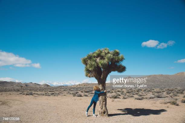 Full Length Of Woman Hugging Tree At Death Valley National Park Against Sky