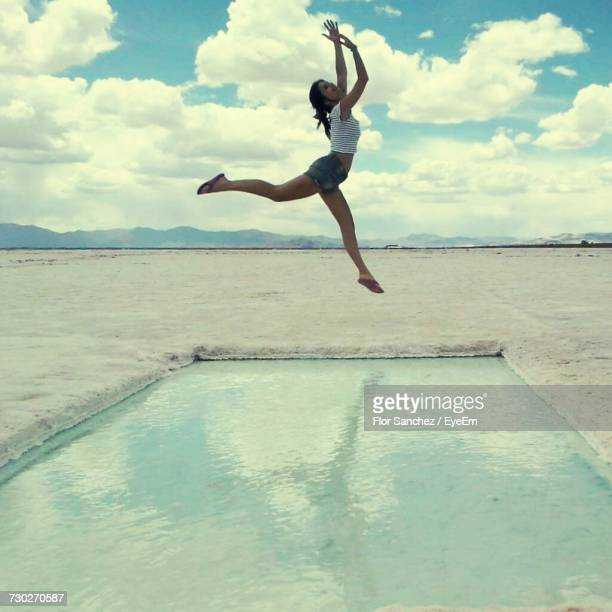 Full Length Of Woman Jumping On Beach Against Sky