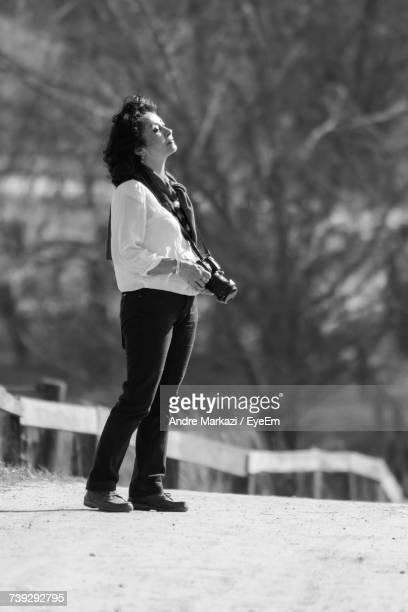 Full Length Of Woman Looking Away While Holding Camera Outdoors