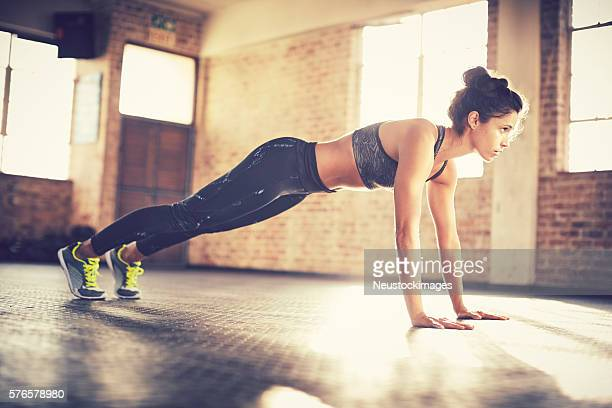 Full length of woman performing push-ups while looking away