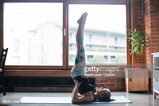 Full Length Of Woman Performing Shoulder Stand By Window At Home