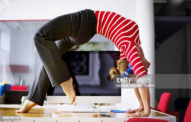Full Length Of Woman Performing Yoga Exercise On Desk In Office
