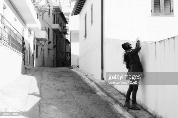 Full Length Of Woman Photographing Building By Street In City
