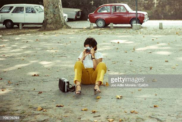 Full Length Of Woman Photographing While Sitting On Road In City
