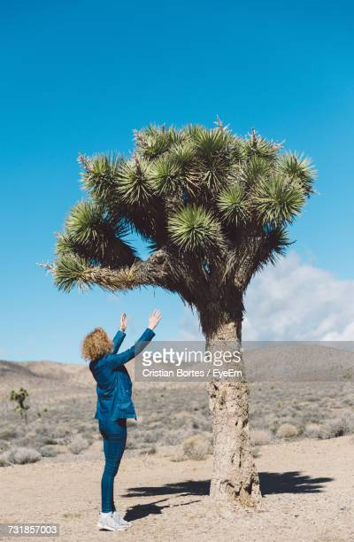 Full Length Of Woman Reaching Towards Tree Against Blue Sky