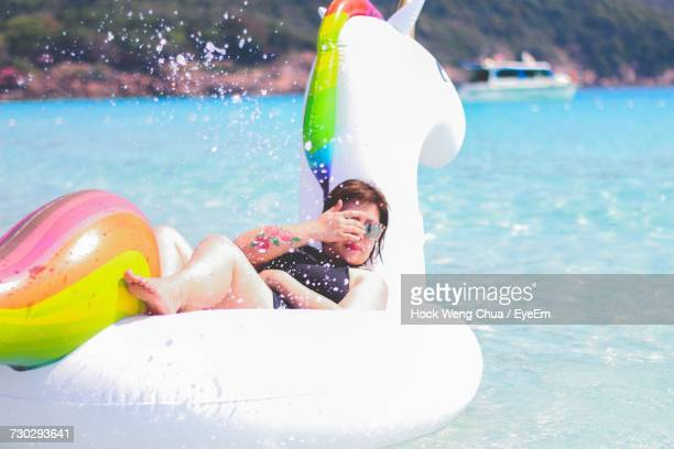 Full Length Of Woman Relaxing On Inflatable Unicorn At Sea