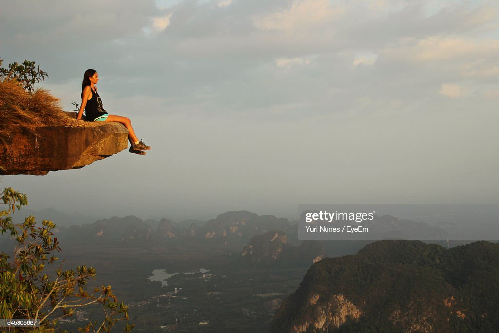 Full Length Of Woman Sitting At The Edge Of Mountain Against Sky During Sunset
