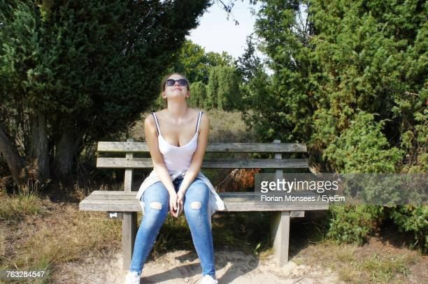 Full Length Of Woman Sitting On Bench By Trees