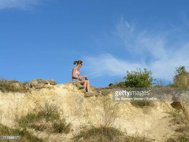 Full Length Of Woman Sitting On Cliff Against Sky