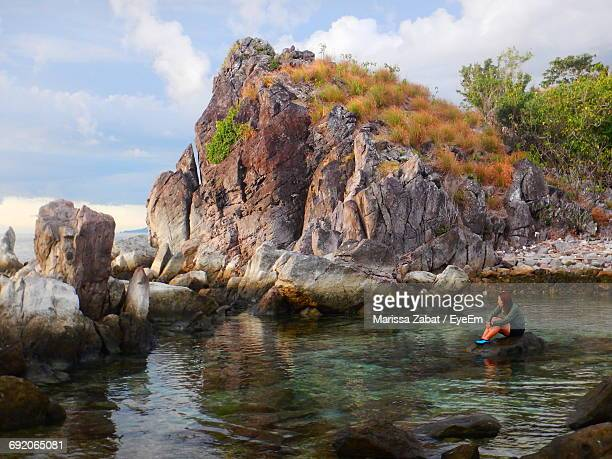 Full Length Of Woman Sitting On Rock Amidst Lake Against Mountain