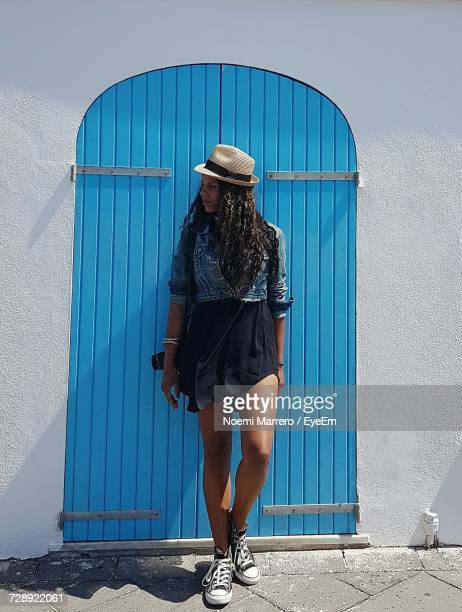 Full Length Of Woman Standing Against Closed Blue Door