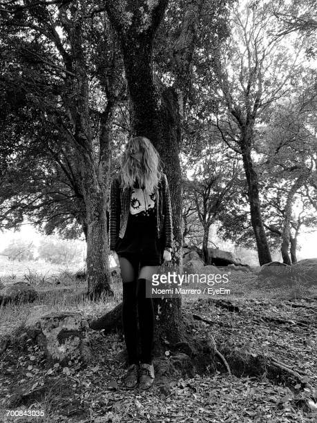 Full Length Of Woman Standing By Tree Trunk In Forest