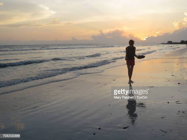 Full Length Of Woman Standing On Shore At Beach During Sunset