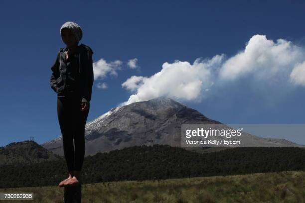 Full Length Of Woman Standing On Wooden Post Over Field Against Popocatepetl
