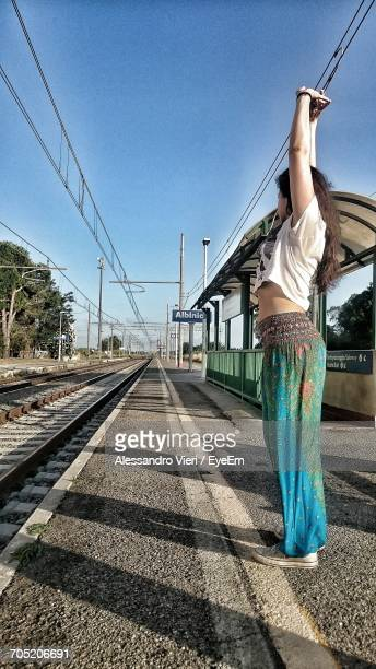 Full Length Of Woman Standing With Arms Raised On Railway Station Platform Against Clear Blue Sky