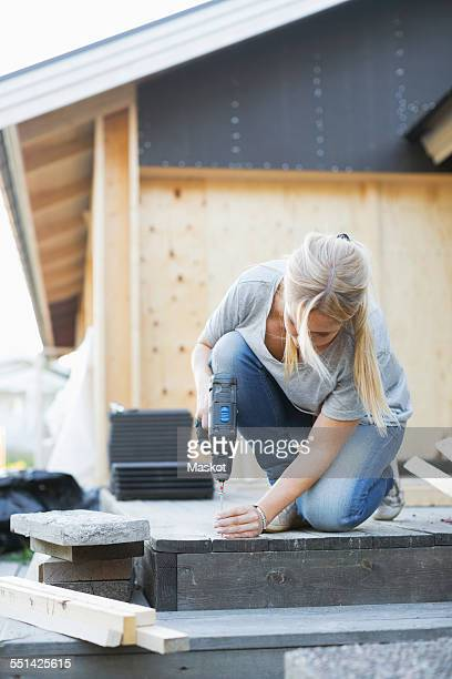 Full length of woman using cordless screwdriver nail into floorboard