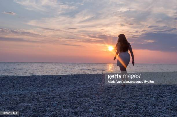 Full Length Of Woman Walking On Sea Shore At Beach Against Sky During Sunset