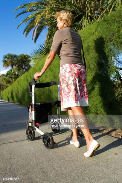 Full Length Of Woman With Mobility Walker Walking On Footpath During Sunny Day