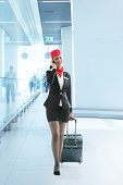 Full length of young air stewardess pulling luggage while answering mobile phone in airport