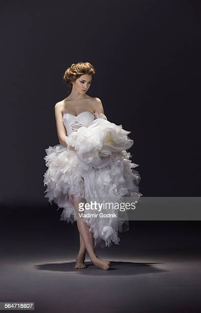 Full length of young bride in wedding dress standing over colored background