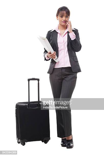 Full length of young business woman with luggage using cell phone