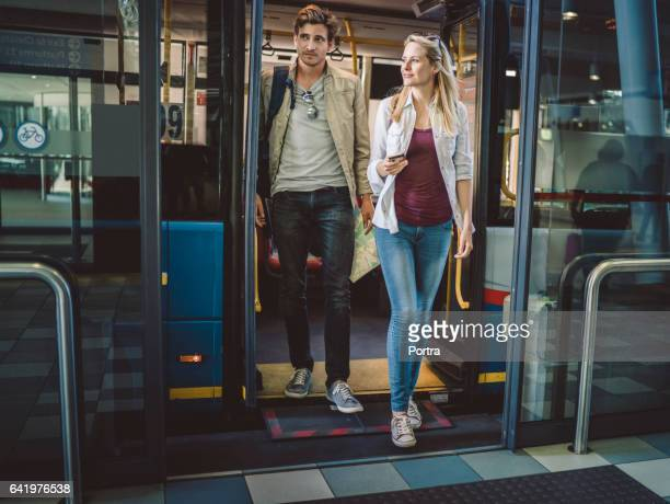 Full length of young couple disembarking from bus