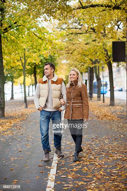 Full length of young couple walking on street during autumn
