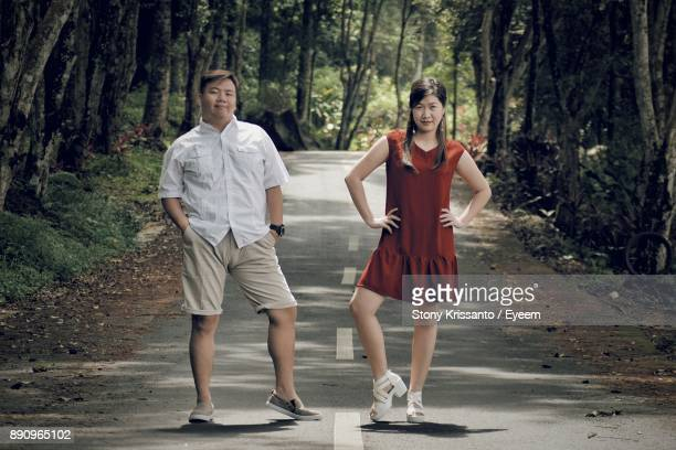 Full Length Of Young Man And Woman Standing On Road In Forest