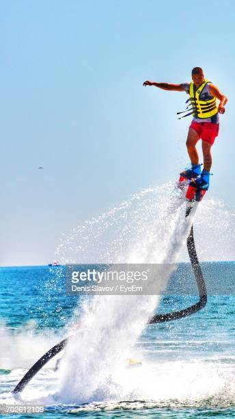 Full Length Of Young Man Flyboarding At Sea Against Clear Sky