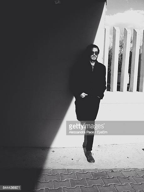 Full Length Of Young Man Leaning On Wall At Sidewalk