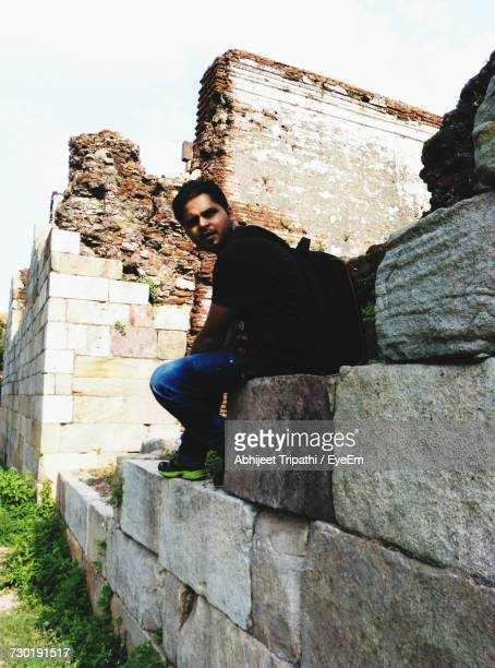 Full Length Of Young Man Looking Away While Sitting On Stone Wall