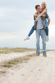 Full length of young man piggybacking woman on trail at field