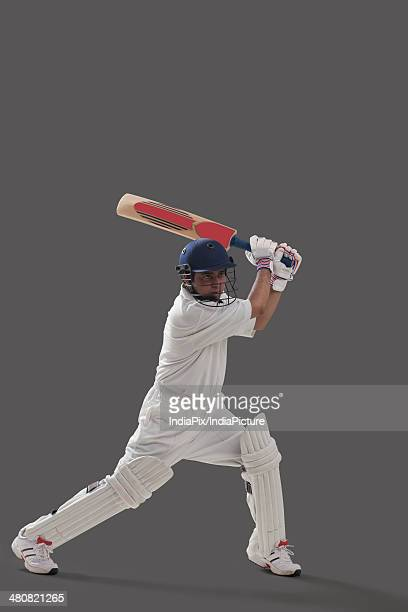 Full length of young man playing cricket over gray background