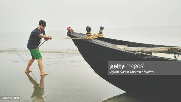 Full Length Of Young Man Pulling Moored Boat At Beach Against Clear Sky