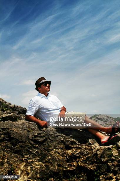 Full Length Of Young Man Sitting On Rocks Against Sky