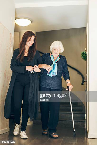 Full length of young woman assisting grandmother to walk by steps